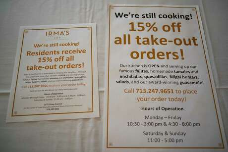 Posters offering deals to customers sit on a table at Irma's Southwest, Wednesday, March 18, 2020, in downtown Houston.