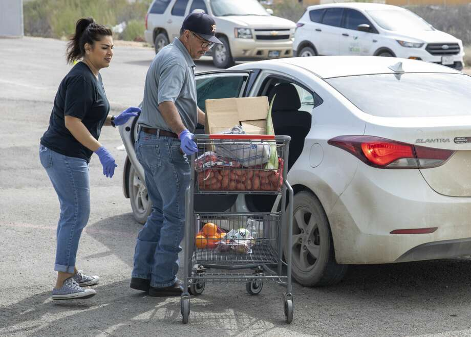 West Texas Food Bank employees Martha Carrasco, from left, and Eloy Salcido bring food from the pantry out to a car Wednesday, March 18, 2020 at the West Texas Food Bank in Odessa. Photo: Jacy Lewis/Reporter-Telegram