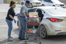 West Texas Food Bank employees Martha Carrasco, from left, and Eloy Salcido bring food from the pantry out to a car Wednesday, March 18, 2020 at the West Texas Food Bank in Odessa.