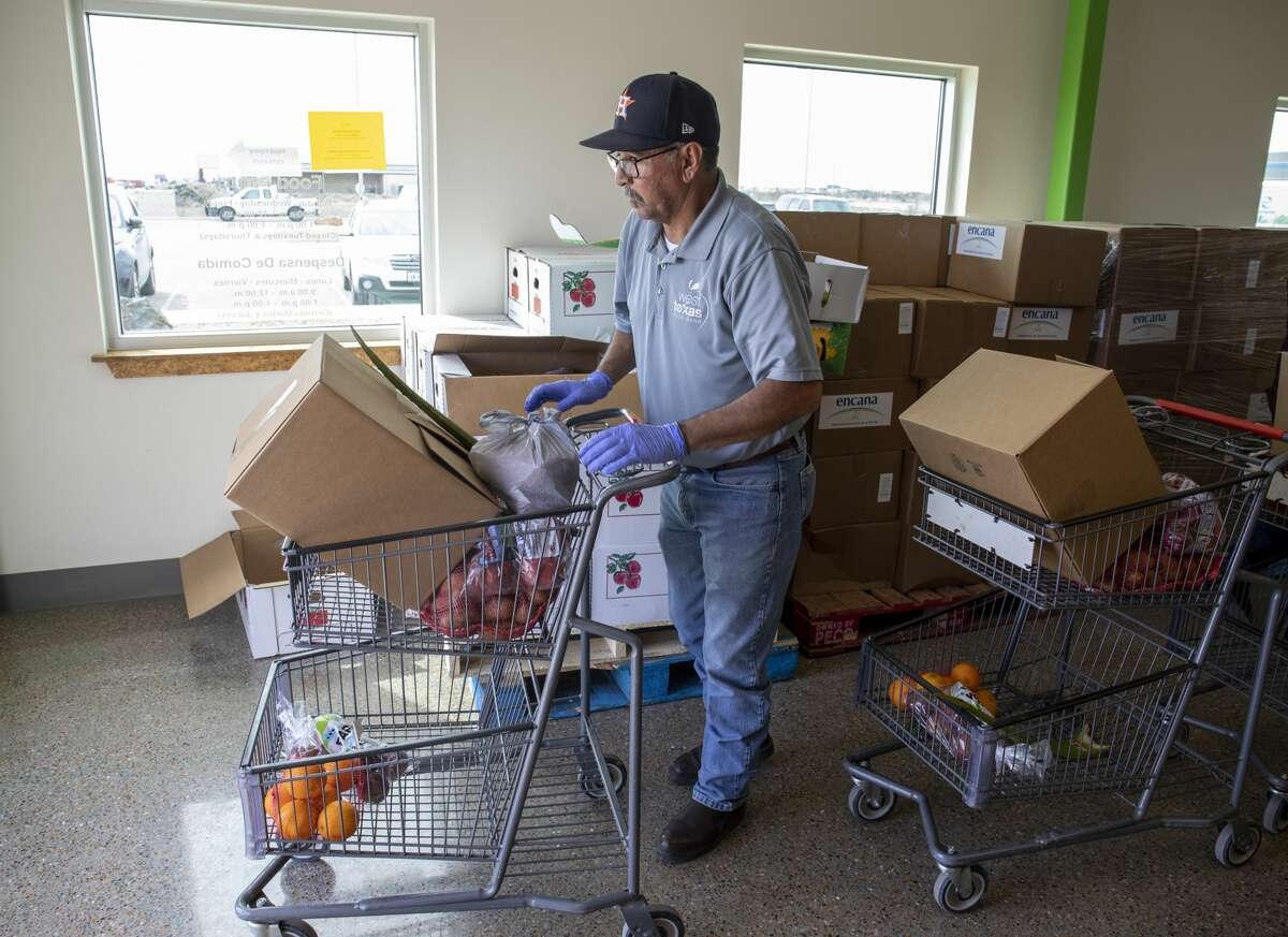 West Texas Food Bank employee Eloy Salcido takes groceries from the pantry out to a car Wednesday, March 18, 2020 at the West Texas Food Bank in Odessa.