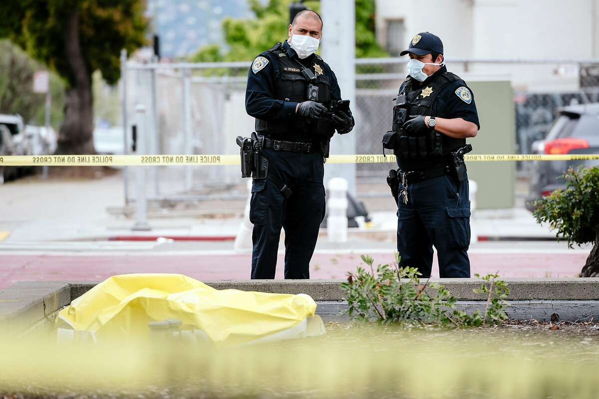 BART police officers wear face masks while investigate a deceased male outside the Lake Merritt BART station in Oakland, California, US, on Wednesday, March 18, 2020.