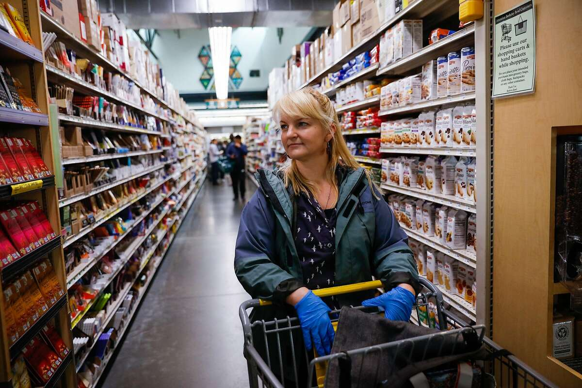 Oakland resident Shannon Ratay waits in line after shopping food for people in need at Berkeley Bowl on Sunday, March 15, 2020 in Berkeley, California. Ratay shopped for people who were in need of food but could not leave their house due to the coronavirus.