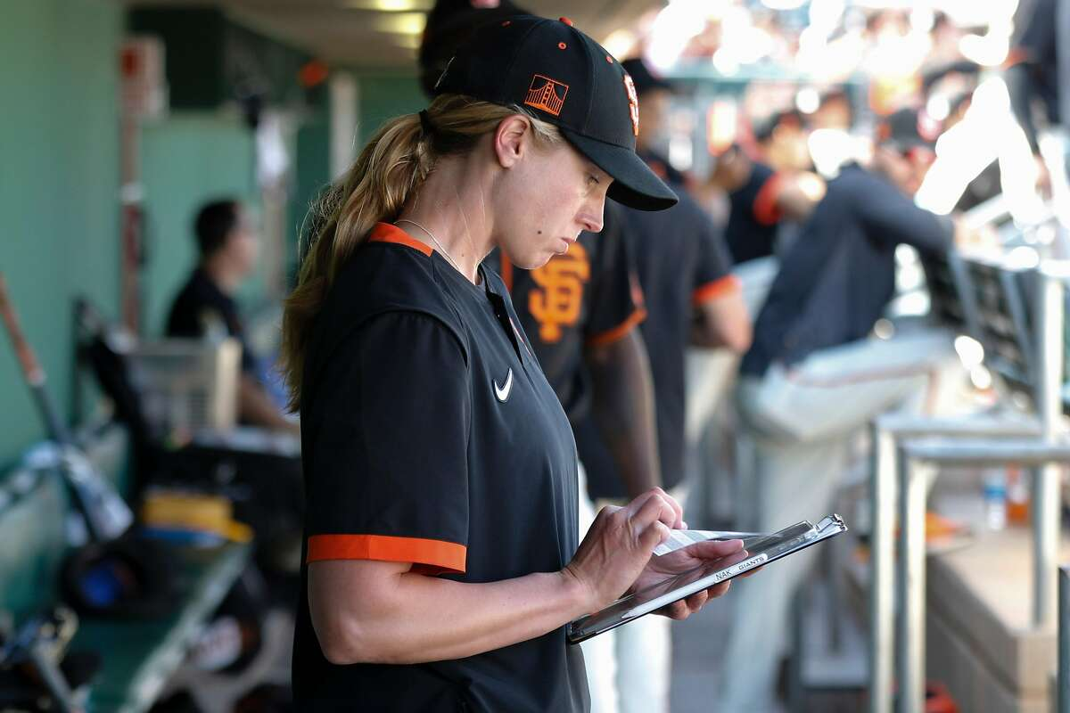 San Francisco Giants' coach Alyssa Nakken look over notes in the dugout before their game with the Cleveland Indians at Scottsdale Stadium Thursday, March 5, 2020, in Scottsdale, Arizona.