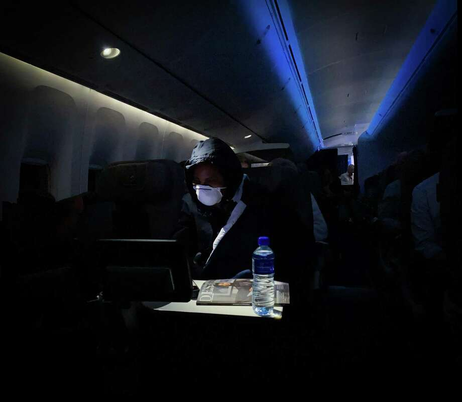 A passenger wears a face mask as a preventive measure during a flight from Johannesburg to Frankfurt on March 17, 2020. A South African businessman said he was diagnosed with the coronavirus days after attending a large party in Westport, where there are now at least 20 confirmed cases of the illness. Photo: Guillem Sartorio / Getty Images / AFP or licensors