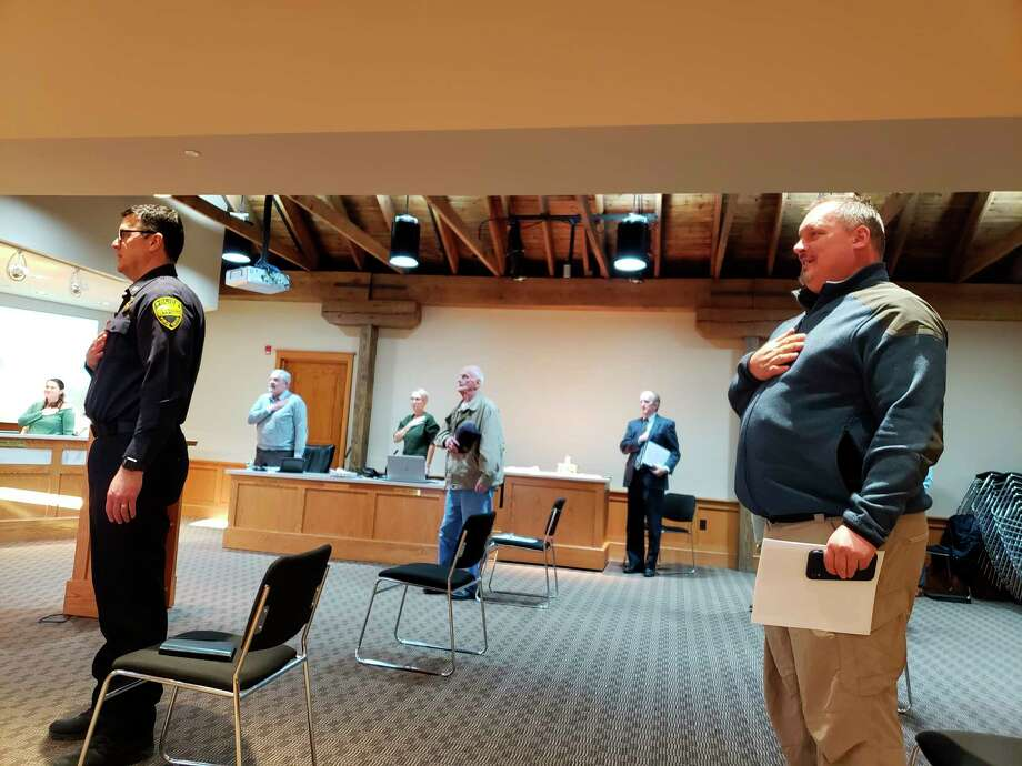 Manistee City Councilmembers and audience members alike sat, stood and presented six feet apart Tuesday evening. Attendees are pictured reciting the Pledge of Allegiance. (Arielle Breen/News Advocate)