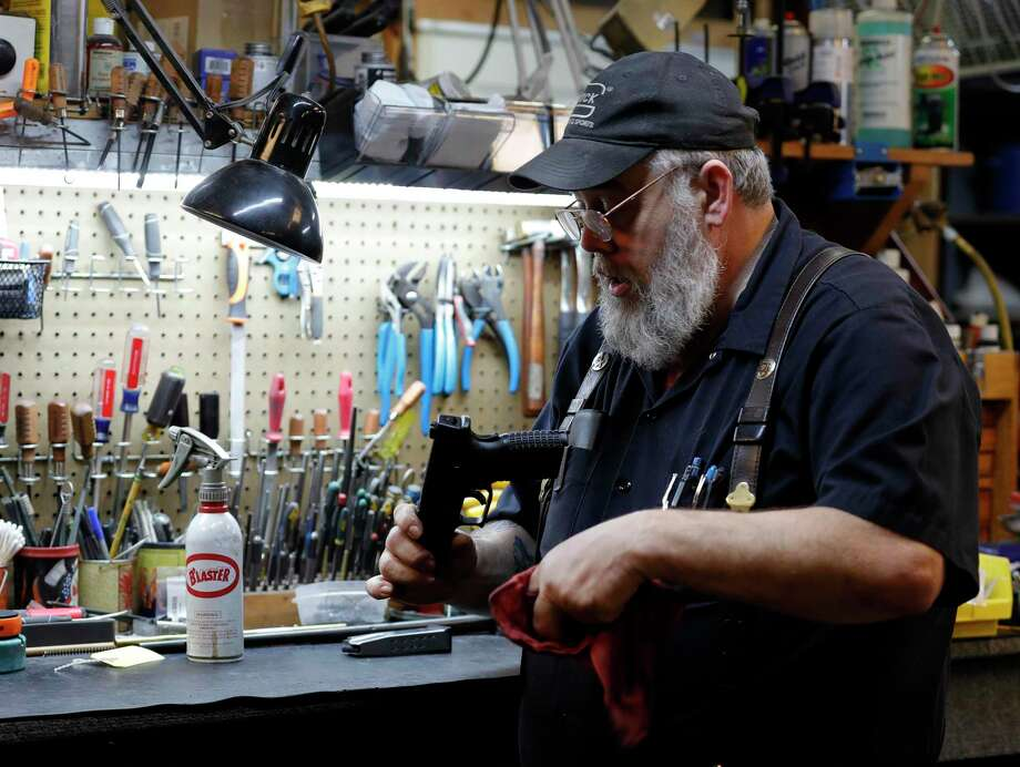 Allen Perry, owner of Mac Daddy's Cigars and Guns, cleans and repairs a Springfield XDM, Wednesday, March 18, 2020, in Conroe. Photo: Jason Fochtman,  Houston Chronicle / Staff Photographer / Houston Chronicle  © 2020