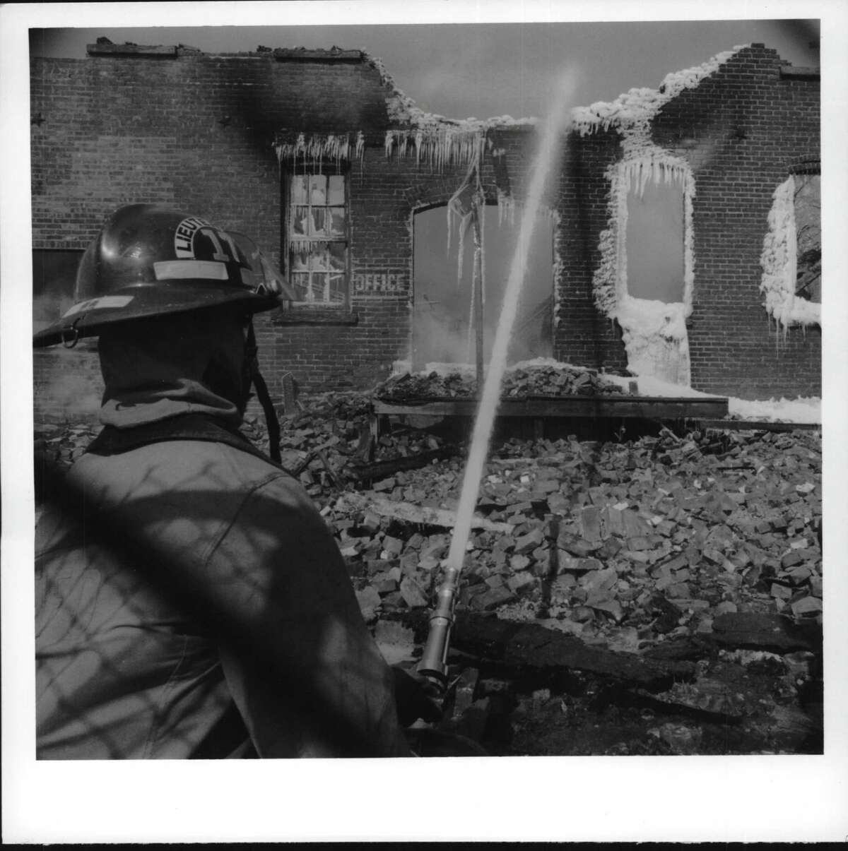 A fire lieutenant from Hoosic Falls fires a deluge on the smoldering ruins of the warehouse that burned early Friday morning. March 19, 1993 (Paul Kniskern/Times Union Archive)