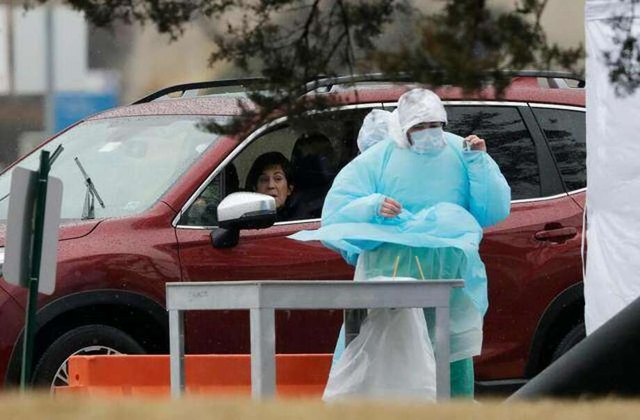 Medical personnel at Advocate Lutheran General Hospital, conduct drive-thru COVID-19 testing in Park Ridge, Ill., Wednesday, March 18, 2020. (AP Photo/Nam Y. Huh)