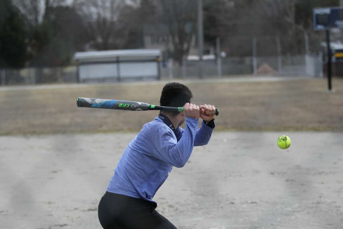 North Huron multi-sport student athlete De'Andre Morris hits softballs around the Bad Axe Little League field with a group of friends earlier this week. High school sports are still on hold due to the coronavirus outbreak as Michigan schools remain closed through at least April 6.