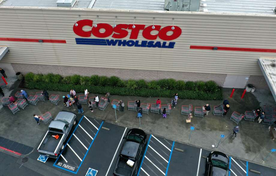 FILE - Hundreds of people line up to enter a Costco store on March 14, 2020 in Novato, California. Some Americans are stocking up on food, toilet paper, water and other items after the World Health Organization (WHO) declared Coronavirus (COVID-19) a pandemic. The company issued new guidelines for customers on April 1, including reduced hours and closures of certain departments. Photo: Justin Sullivan/Getty Images
