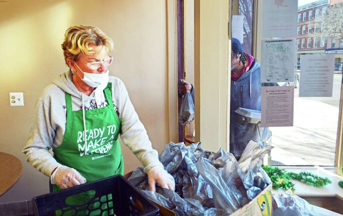 St. Vincent de Paul Middletown dining services manager Lisa Magee-Corvo serves people walking into the entryway of the soup kitchen in the North End. During the coronavirus pandemic, clients are allowed one lunch per day (with a sandwich to take home for dinner) between 11 a.m. and 12:30 p.m. Monday to Saturday.