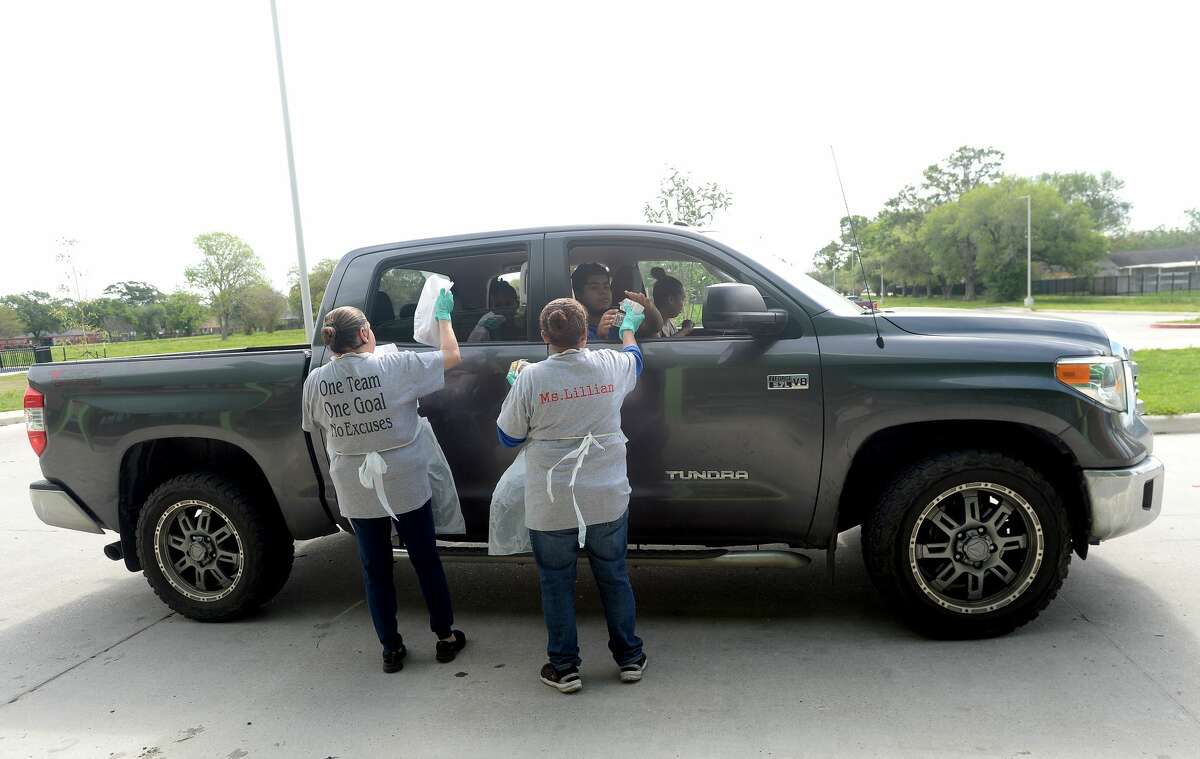 Lillian Ward and Maregarita Figuero distribute lunches at Sam Houston Elementary on the first day of breakfast and lunch distribution for Port Arthur ISD students, as well as any children 18 and under who arrive to get a meal. Photo taken Wednesday, March 18, 2020 Kim Brent/The Enterprise