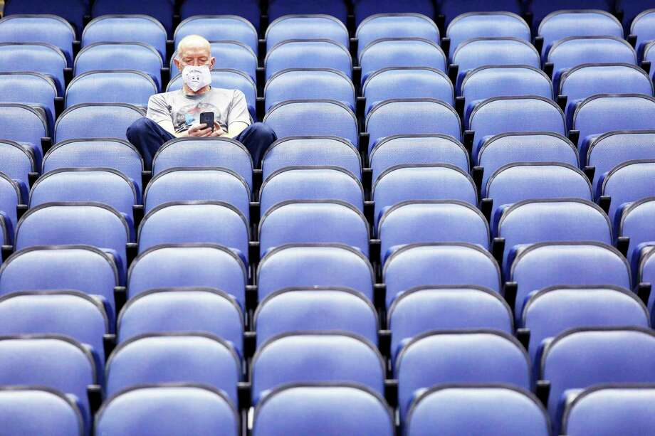Mike Lemcke, from Richmond, Va., sits in an empty Greensboro Coliseum after the NCAA college basketball games were canceled at the Atlantic Coast Conference tournament in Greensboro, N.C., Thursday, March 12, 2020. The sweeping suspension of sports due to concern over the coronavirus has affected Michigan high school athletics as well, including in Manistee County.  (AP Photo/Ben McKeown) / Copyright 2020 The Associated Press. All rights reserved