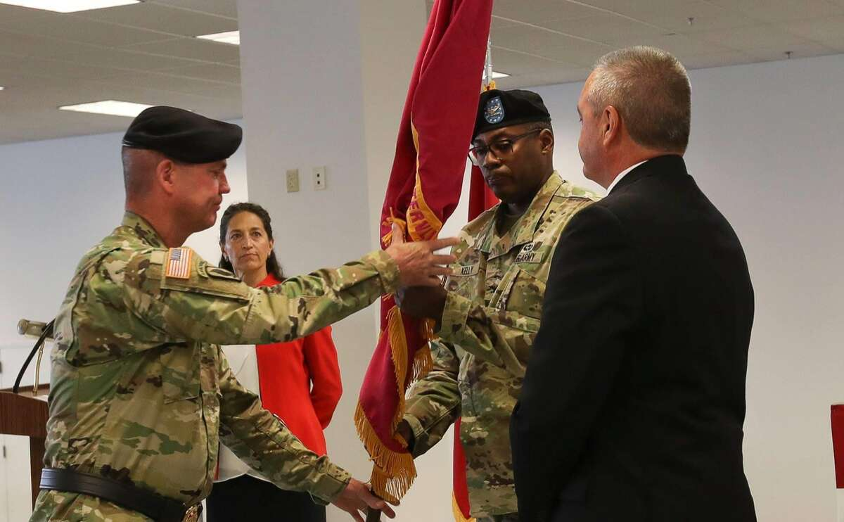 Maj. Gen. Daniel G. Mitchell, left, passes the Watervliet Arsenal colors to Col. Milton G. Kelly, center, during COL. Kelly's assumption of command ceremony on August 21, 2018.