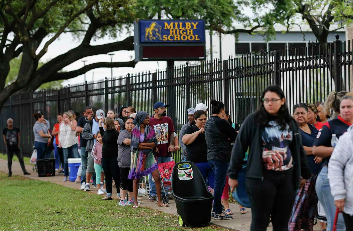 People wait in line for food distribution at Milby High School on Monday, March 16, 2020, in Houston. HISD schools are closed to prevent further spread of the new coronavirus, which was declared a pandemic by the World Health Organization last week. The school district, in partnership with the Houston Food Bank School Market program, will offer daily food distribution at five area high schools through Friday, March 20.