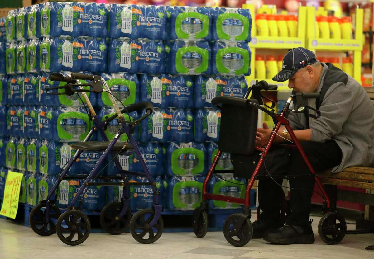 A man sits next to a pallet of water at Food Town, Wednesday, March 18, 2020, in New Caney. The grocery store established an elderly-only hour for shoppers 65-years or older from 7 a.m. to 8 a.m.