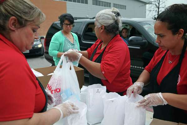 San Antonio Independent School District personnel hand out lunch bags on Monday, March 16, 2020, at Lanier High School for students staying at home while schools are closed during the coronavirus pandemic.