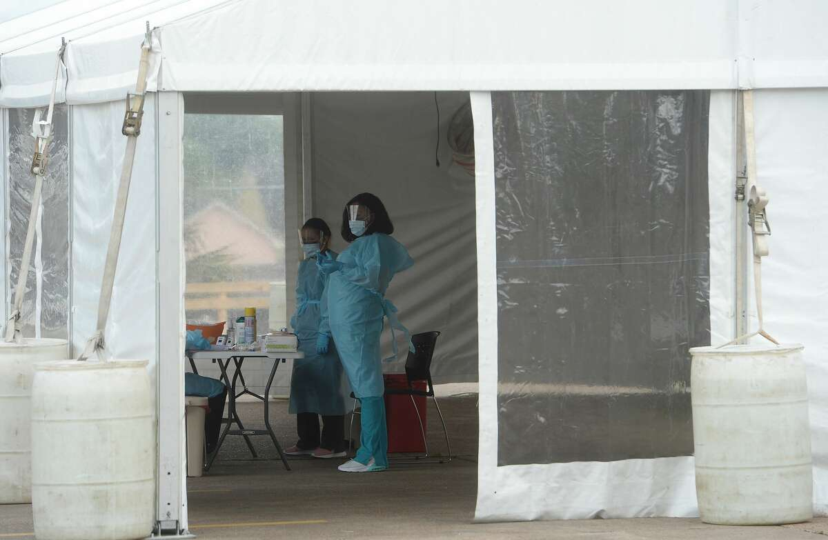 Medical personnel work inside a tent set up in the back lot of Legacy Community Health on N. Eleventh Street in Beaumont offering COVID-19 testing after screening and also doing flu testing. The clinic is the first private screening unit set up in Jefferson County. Photo taken Wednesday, March 18, 2020 Kim Brent/The Enterprise