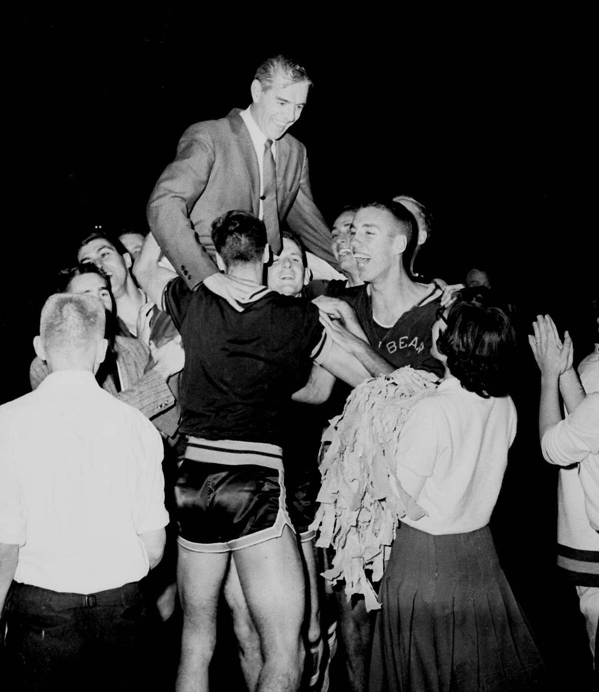 A smiling coach Pete Newell is hoisted to shoulders of members of the California Bears basketball team March 21, 1959 after they won a close, 71-70 decision over West Virginia at Louisville,Ky. to became NCAA champs.