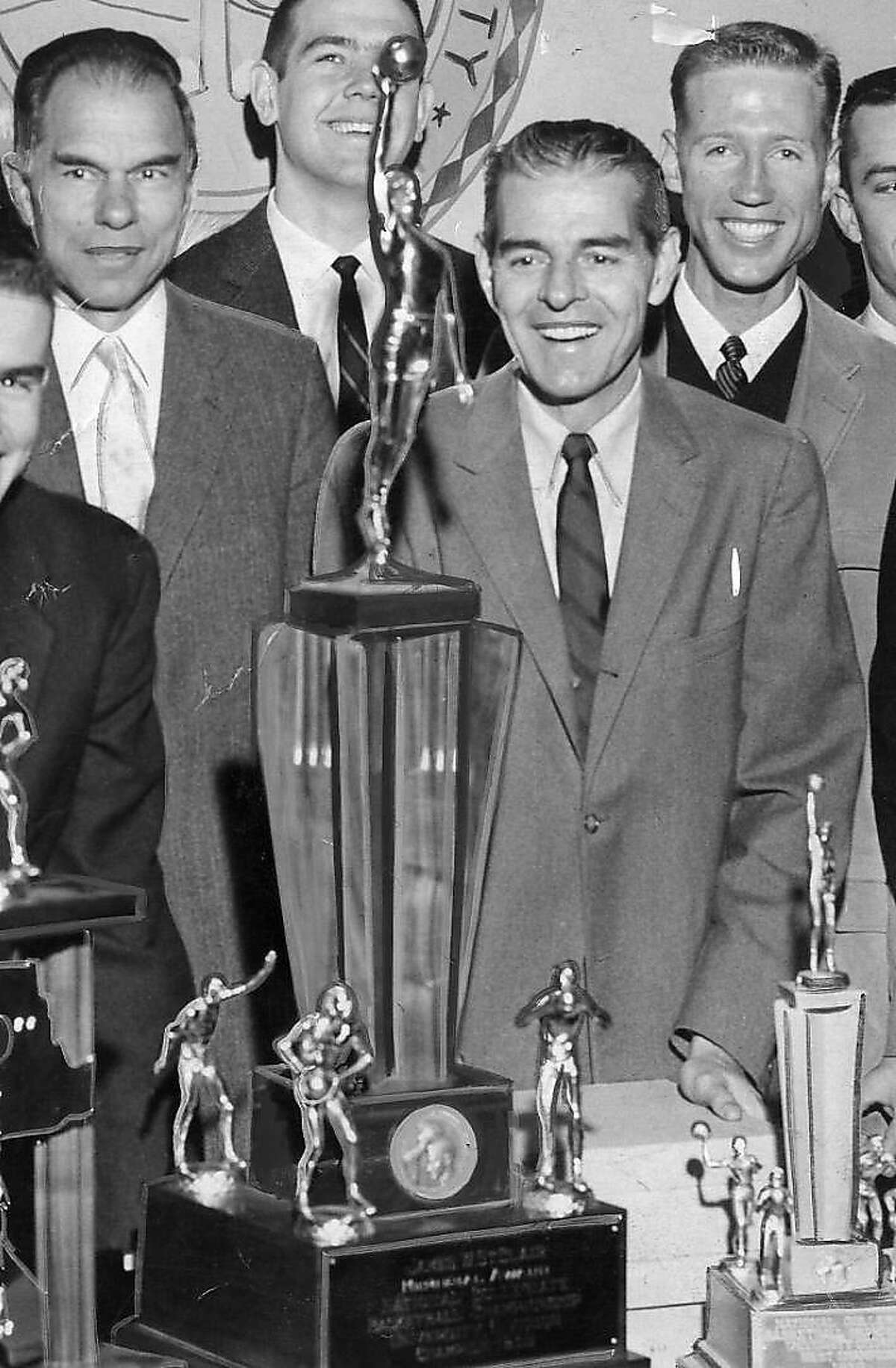 Pete Newell, to right of the big NCAA championship trophy, stands next to UC Berkeley Chancellor Glenn Seaborg, left, on March 23, 1959 after Cal won the 1959 NCAA men's basketball championship.