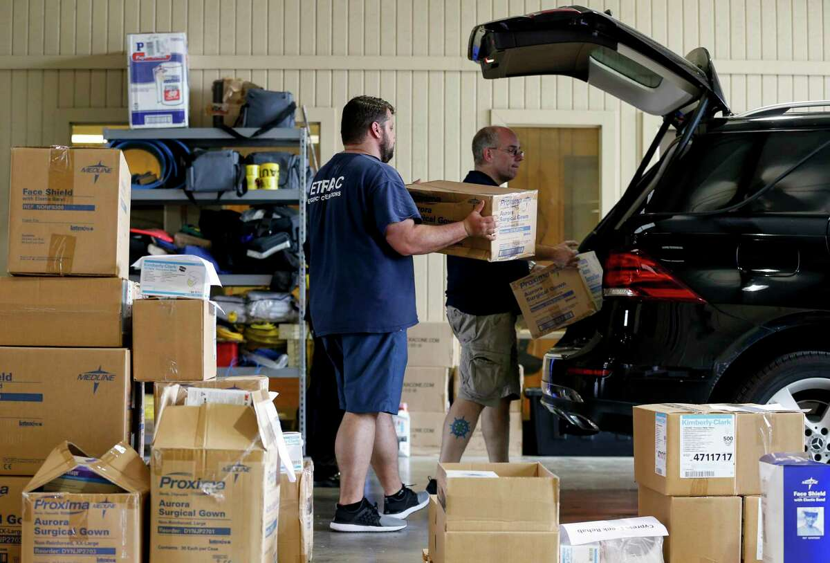 SETRAC Emergency Operations' Austen McMillin, left, and Donald Morrison, center, load up medical supplies into the trunk of an SUV going to a local healthcare facility, at the Strategic National Stockpile distribution site Wednesday, March 18, 2020, in Houston.