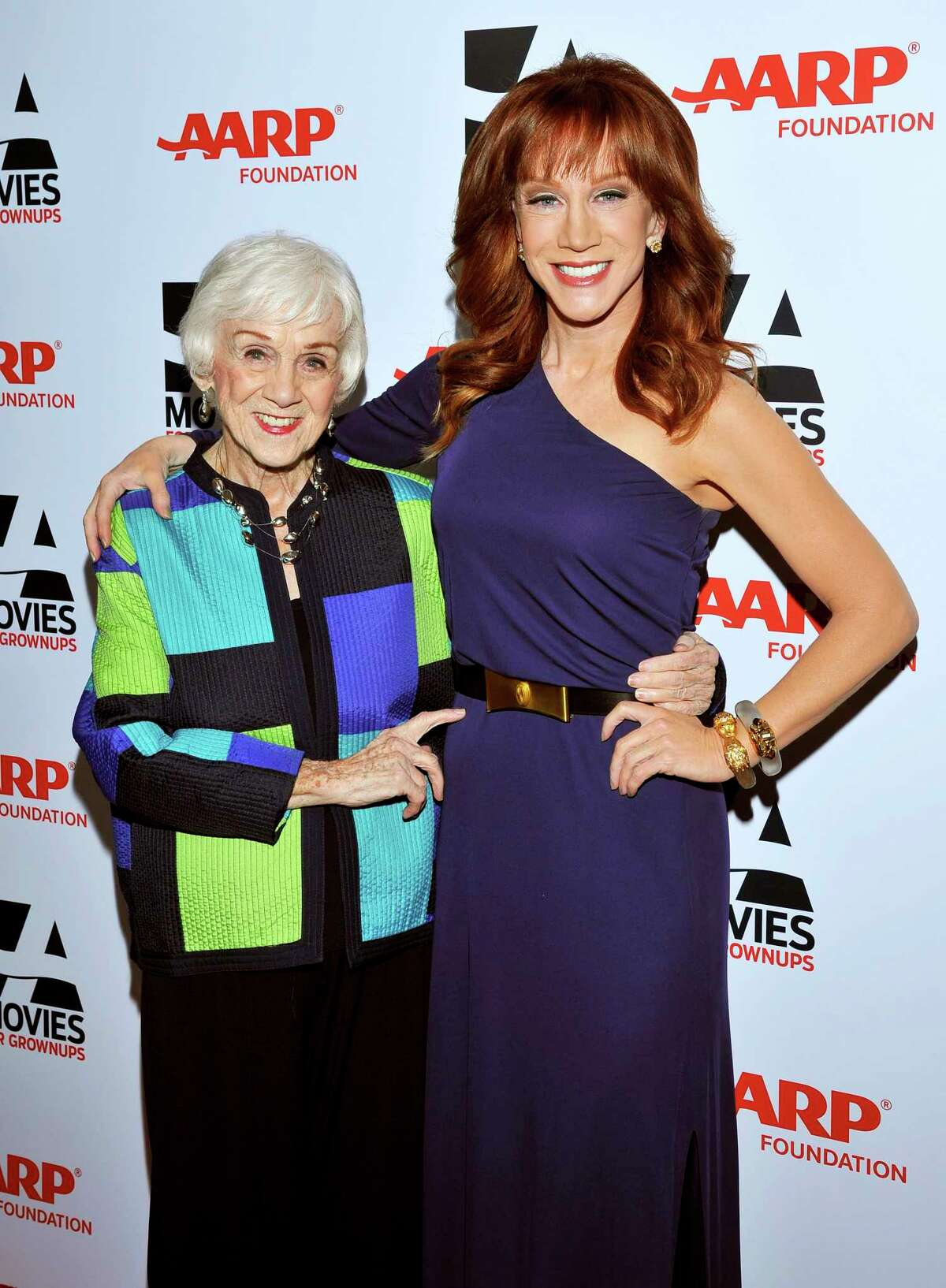 FILE - In this Feb. 10, 2014 file photo, Kathy Griffin, right, and mother Maggie Griffin arrive at the 2014 AARP's Movies for Grownups Gala, in Beverly Hills, Calif. Maggie Griffin, the mother of comedian Kathy Griffin, who inspired many of the jokes in her famous daughter's standup routines, died Tuesday, March 17, 2020. She was 99. (Photo by Vince Bucci/Invision for AARP Media/AP Images, File)