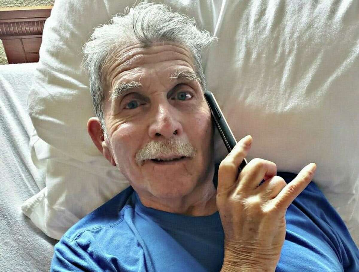 Richard Alvarado, 72, talks on the phone with his daughter from Bayou Pines Care Center in La Marque. With family members barred from visiting, nursing home staff are trying to facilitate phone and video calls.
