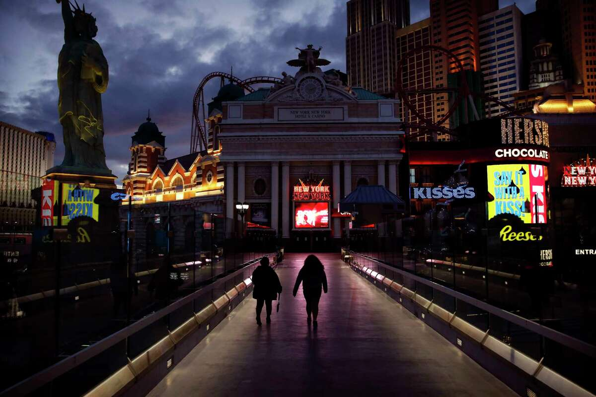 People walk along the Las Vegas Strip devoid of the usual crowds after casinos were ordered to shut down due to the coronavirus outbreak, Wednesday, March 18, 2020, in Las Vegas.