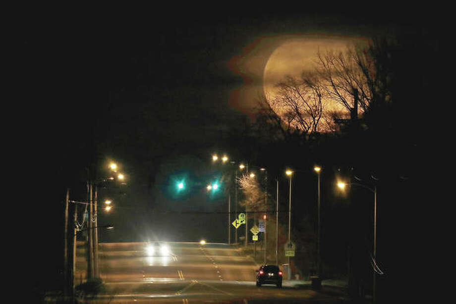 Cars appear dwarfed as a nearly full moon rises in the distance. The planets and moon are providing some early morning entertainment this week as Mars, Jupiter, Saturn and a crescent moon cluster together in the southeastern sky just before daybreak. Mercury will peak above the horizon.
