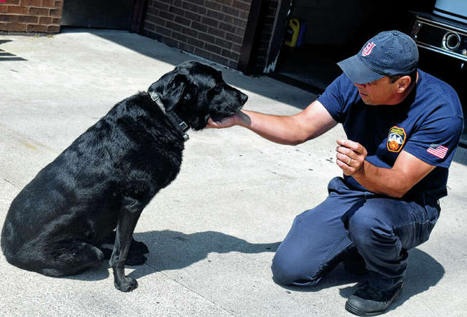 Engine driver Jim Williams plays with Smokey in September at the Jacksonville Fire Department substation. Photo: Samantha McDaniel-Ogletree   Journal-Courier