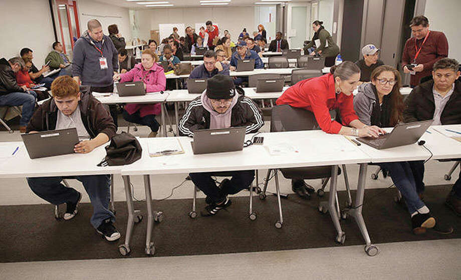 Workers apply for unemployment benefits. Fearing a widespread health crisis, many states have shuttered schools and restaurants and put limits on event attendance. Photo: Marcio Jose Sanchez   AP