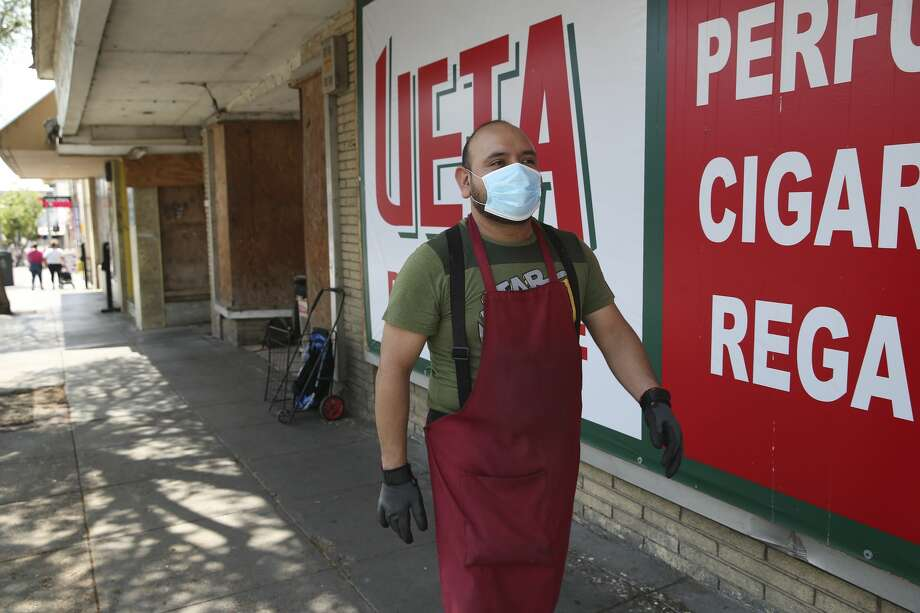 Adrian Torrez, 41, wears protection as he walks between stores in downtown Laredo, Texas, Wednesday, March 18, 2020. Torrez, who works at a shoe retail and wholesale business said he has seen a drop in business in response to the coronavirus threat. The majority of businesses in the downtown area sell to the Mexican market. He said that his boss required them to wear the protective gear. Photo: Jerry Lara/San Antonio Express-News