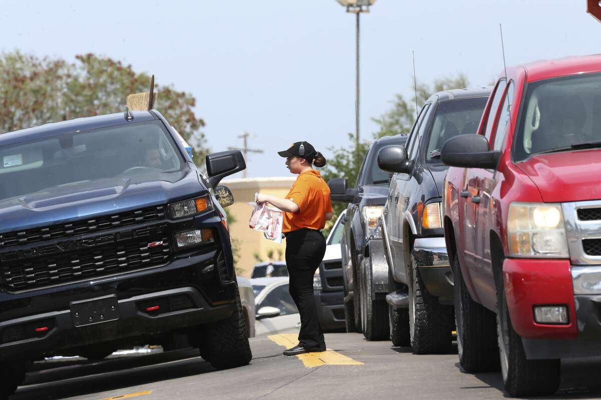 A Whataburger employee delivers meals to vehicles at a location in Laredo, Texas, Wednesday, March 18, 2020. Most major chain restaurants in Laredo closed their dining area and opened only with drive-thru, delivery or takeout service ahead of a lockdown order issued by the City of Laredo. The order takes effect at midnight Wednesday.