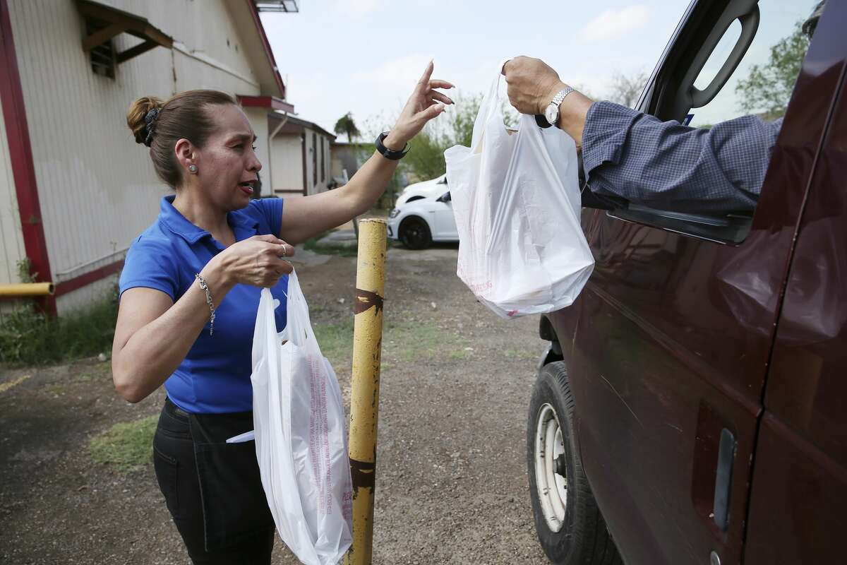 Dora Almanza delivers an order at Paulita's Mexican Restaurant on Jaime Zapata Memorial Highway in Laredo, Texas, Wednesday, March 18, 2020. The City of Laredo issued a lockdown of in response to the coronavirus threat on Tuesday. The order goes into effect at midnight Wednesday and will extend for 14 days. It prohibits the gathering of 10 or more persons and closes malls, entertainment centers, fitness centers and banquet halls. It allows restaurants to open only with drive-thru, delivery or take out service. Essential businesses like medical facilities, veterinarian and grocery establishments are allowed. Offices spaces and places of employment can remain open as long the 10-person rule is followed. Violation of the carries a fine that ranges from $50 to $2,000. The Laredo Police Department will enforce the order. Paulita's owner Jorge Santa Anna said that he would try out the takeout option but after seeing a drop in business starting on Tuesday, he thinks he'll have to close for the duration of the order.