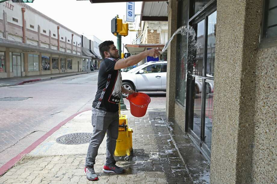 Luis Fernando Contreras, 23, washes windows at a downtown Laredo, Texas business, Wednesday, March 18, 2020. The City of Laredo issue a lockdown in response to the coronavirus threat that will take effect midnight Wednesday. The two-week mandatory lockdown will keep the public from gathering in groups of more than 10 and restaurants are only allowed to have takeout, delivery or drive-thru service. Citizens are allowed to go to grocery stores, hospitals and work. Photo: Jerry Lara/San Antonio Express-News