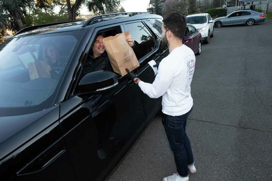 A customer picks up takeout food from a Seattle restaurant on March 16, 2020. The Chef's Warehouse, a Ridgefield, Conn. supplier of gourmet food and ingredients in Seattle, New York City and several other markets nationally, drew $100 million in cash from an existing credit line in anticipation of restaurant orders plummeting. Photo: Karen Ducey / Getty Images / 2020 Getty Images