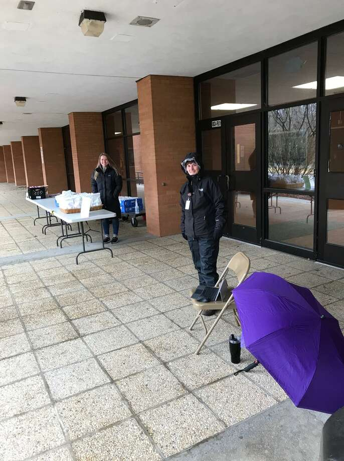 Interim Superintendent Beth Smith dons her rain gear Thursday, March 19, and is ready to distribute food to families at Shelton High School. Photo: Contributed Photo / Connecticut Post