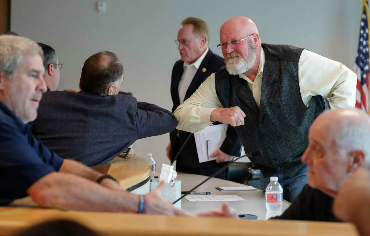 Montgomery County Precinct 2 Commissioner Charlie Riley, right, bumps elbows with State Rep. Steve Toth, R-The Woodlands, during a special session of the Montgomery County Commissioners Court called after county health officials announced the second presumptive positive case of COVID-19, Thursday, March 12, 2020, in Conroe.