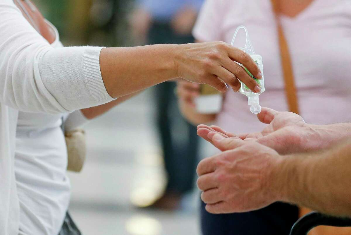 People use hand sanitizer after exiting the international terminal at George Bush Intercontinental Airport on Thursday, March 12, 2020, in Houston. The new coronavirus has been classified as a pandemic by the World Health Organization.