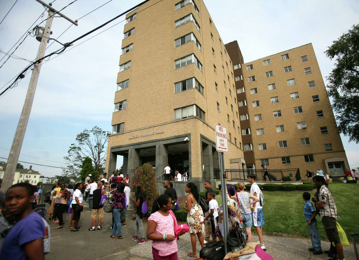 Students and family members wait in line to check in and move in their things at the Bodine Hall dormitory at the University of Bridgeport on Thursday, August 23, 2012.
