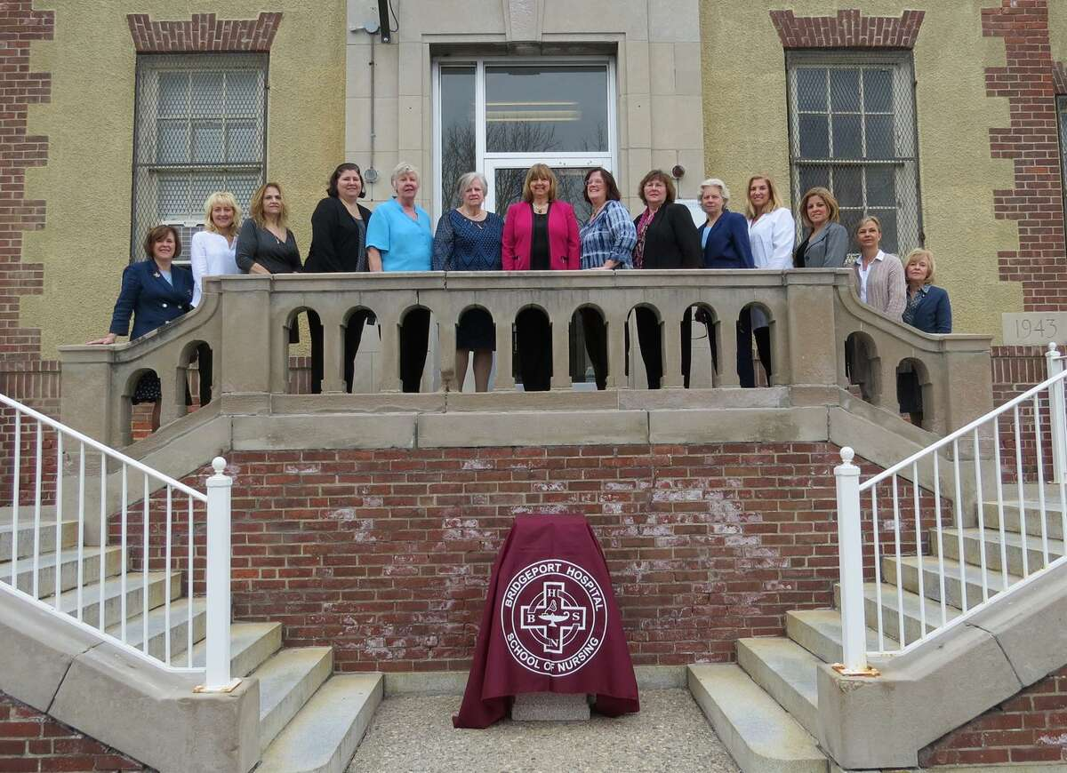 Members of the Bridgeport Hospital School of Nursing faculty, including Director Linda Podolak (center) pose outside the school's main entrance in Bridgeport, Conn.