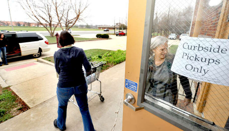 Volunteer workers at the Glen-Ed Pantry Janet Dissler, left, and Brandi Brace, right, bring the food donations to those waiting at their cars Monday instead of them coming inside the building as usual due to precautions over the coronavirus. Photo: Thomas Turney For The Intelligencer