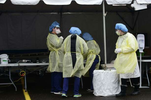 File photo showing hospital workers in personal protective equipment collect samples for coronavirus testing at a drive-up facility in the parking lot at Norwalk Hospital Thursday, March 19, 2020, in Norwalk, Conn. Testing is by appointment only with a doctor's referral.