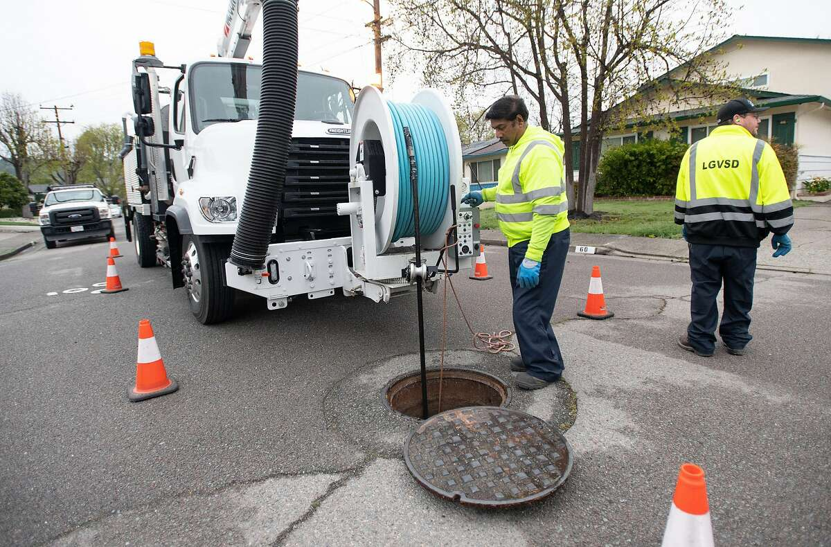 Robert Fernandes (L) and Anthony Asaro (R) with the Las Gallinas Valley Sanitary District demonstrate how their crew performs maintenance on sewer lines in San Rafael, California on March 19, 2020. Sewage spills are on the rise in the era of coronavirus as toilet paper shortages and virus concerns cause people to flush more disinfecting wipes that have been clogging sewer lines.