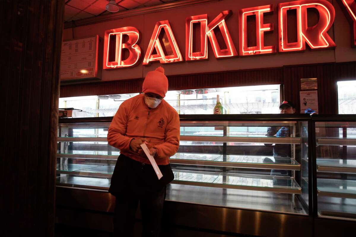 An employee of Junior's Restaurant picks up a paycheck, Thursday, March 19, 2020 in the Brooklyn borough of New York. The restaurant company, which has closed its four locations due to the coronavirus, has laid off 650 of 850 employees.
