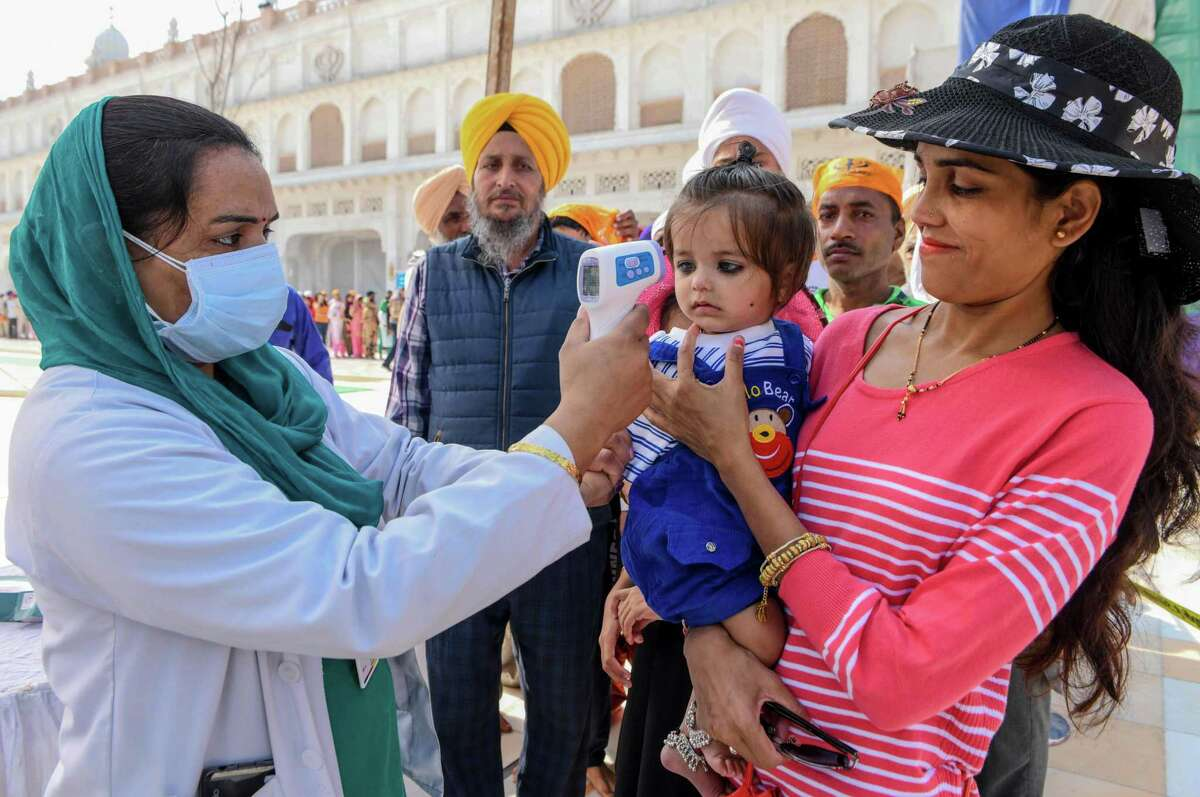 A health worker, left, wearing a facemask checks the body temperature of a baby along with devotees amid concerns over the spread of the COVID-19 novel coronavirus, at the entrance of the Golden Temple in Amritsar, India, on March 18, 2020.