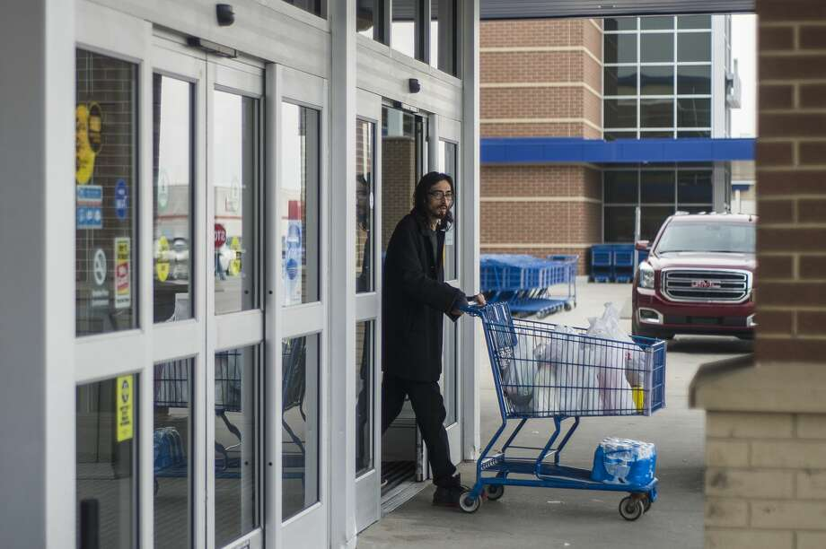 """Derek Reyes of Midland transports groceries to his car after shopping at Meijer Thursday, March 19, 2020 in Midland. """"I'm not concerned about this virus. I'm just living my daily life,"""" Reyes said. (Katy Kildee/kkildee@mdn.net) Photo: (Katy Kildee/kkildee@mdn.net)"""