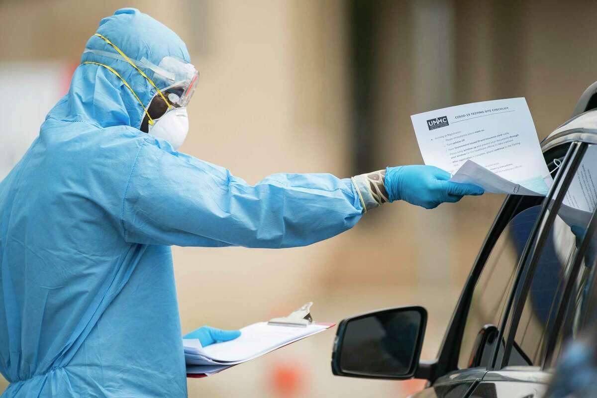 A medical professional asks an initial screening question to a driver in line for drive-thru Cover-19 testing, Thursday, March 19, 2020, at the United Memorial Medical Center in Houston.