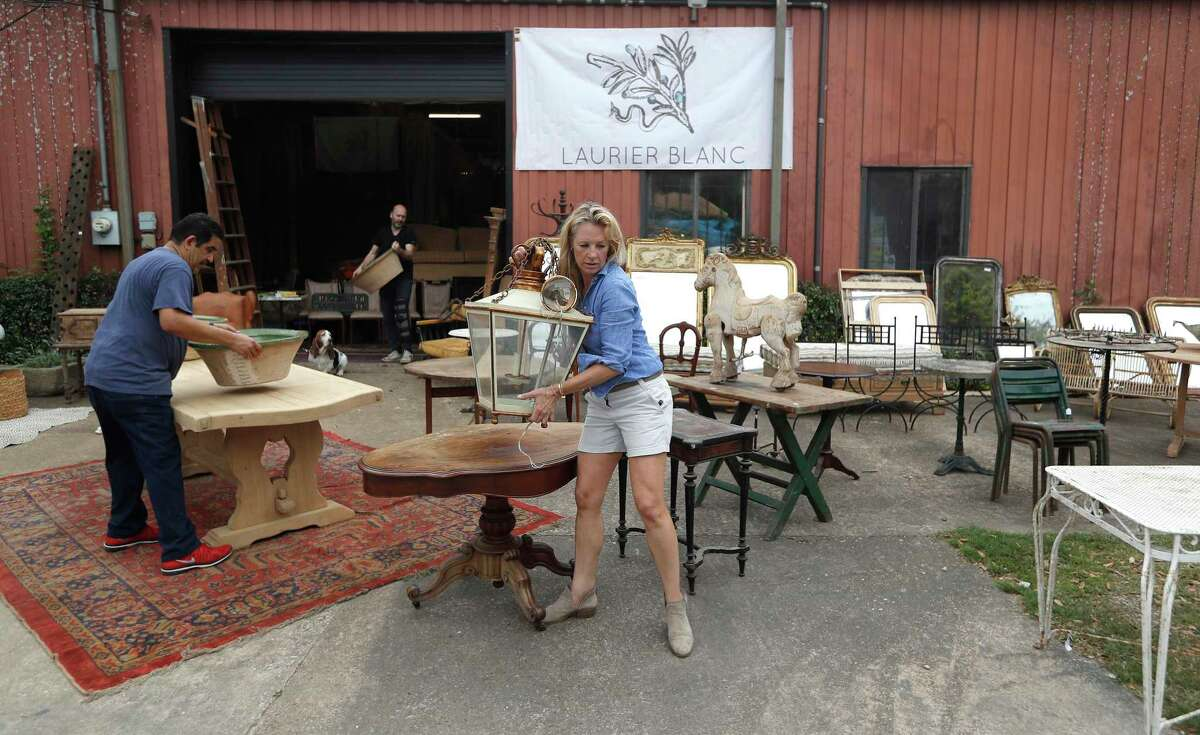 Suzanne Coppola, owner of Laurier Blanc, moves a lantern while she and her staff unpack antiques and decorative arts items she would have had in antique shows Round Top. The spread of the novel coronavirus, or COVID-19, prompted the closure of large events such as the Round Top antiques shows.