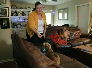 Barbara Bridges, 37, feeds her dog Polly a treat as her other dog Daisy begs for one. Bridges was just laid off from her job as a group sales manager at The Westin Riverwalk, but the company is allowing her to keep her health insurance and could re-hire her if things pick up, on Wednesday, March 18, 2020.